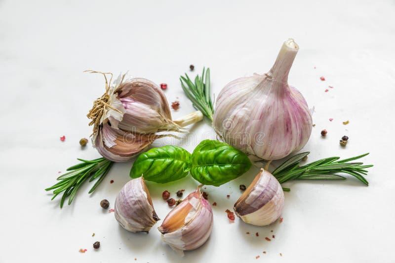 Чеснок, базилик, розмариновое масло и перчинка на белой мраморной предпосылке конец вверх стоковое фото rf
