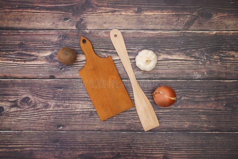Чеснок и лук с деревянной ложкой и разделочная доска на таблице стоковые изображения