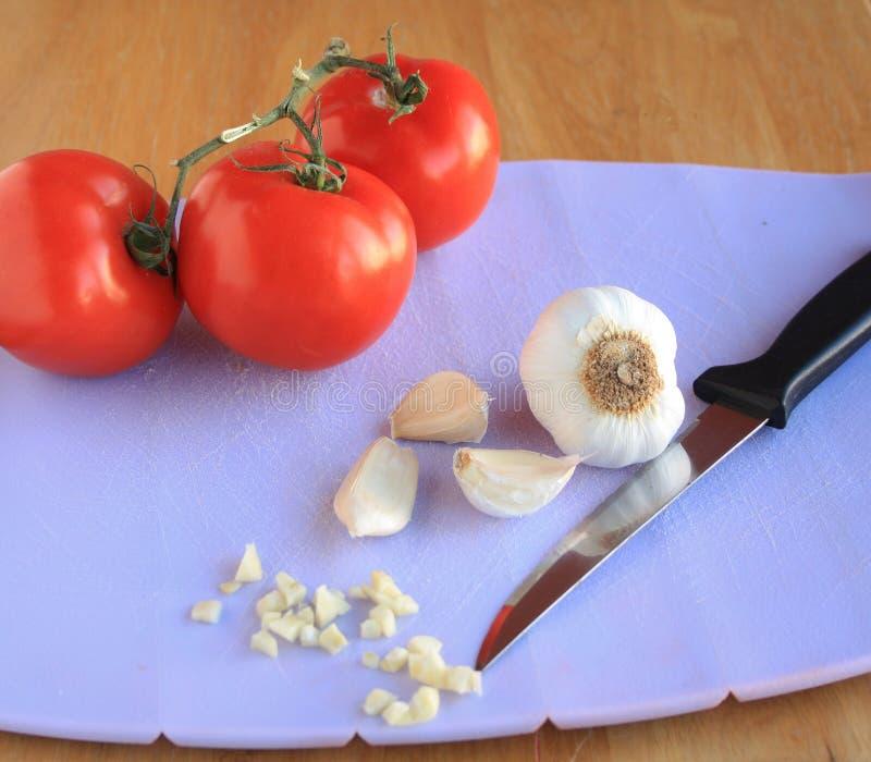 Чеснок и томаты на разделочной доске стоковое фото