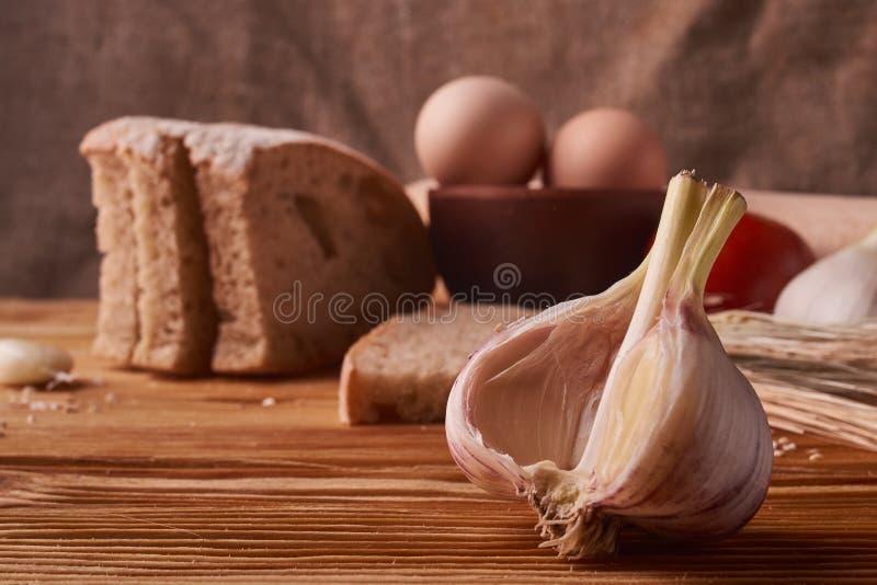 чеснок на деревянном столе с яйцами в ростках шара, томата, battledore и пшеницы глины стоковая фотография