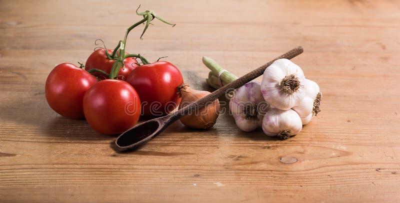 Чеснок лука томата с ложкой стоковая фотография