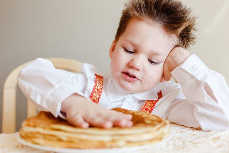 Четырехлетний ребенок касается блинчикам ручки теплым Праздник Maslenitsa стоковое фото