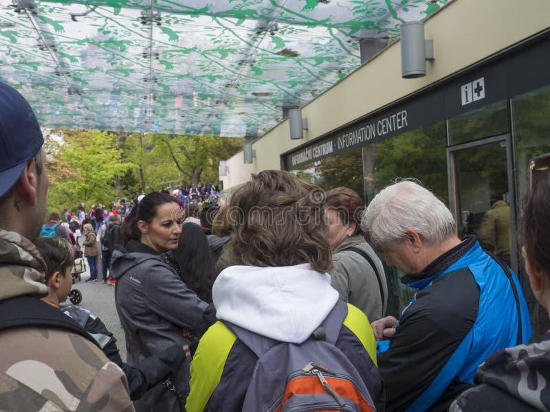 Чехия, Прага, 18-ое мая 2019: Группа людей ждать в очереди на отделе бронирования билета наличных денег, оформляет заказ линия вн стоковое изображение