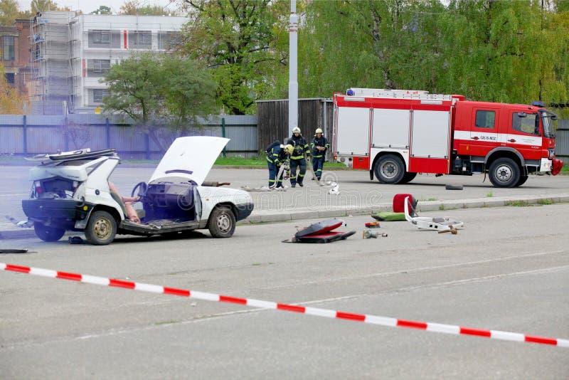 ЧЕХИЯ, PLZEN, 30-ОЕ СЕНТЯБРЯ 2015: Имитация автомобильной катастрофы Пожарные и спасители помогают раненой персоне t стоковое фото