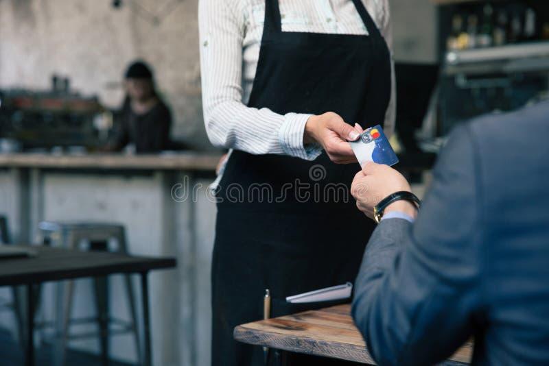 Человек давая кредитную карточку к кельнеру в кафе стоковая фотография rf