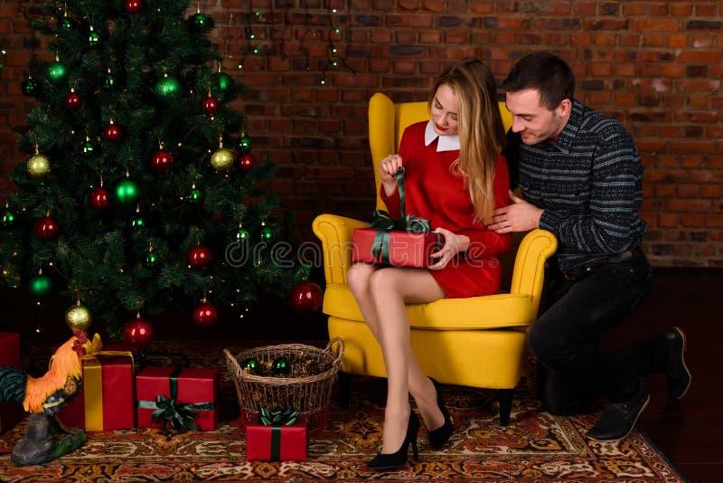 Человек дает девушку подарка около рождественской елки стоковая фотография rf