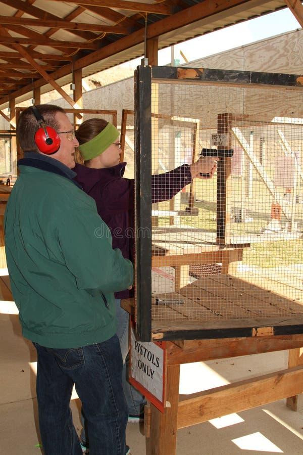 Человек дает подсказки стрельбы к молодой женщине на стрельбище стоковое изображение