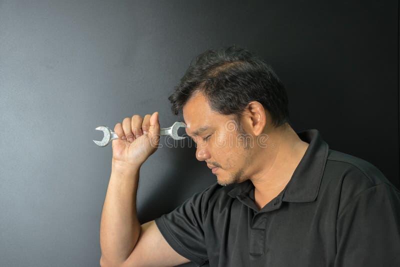 Человек Азии работник держа гаечный ключ в темном стиле стоковые фото