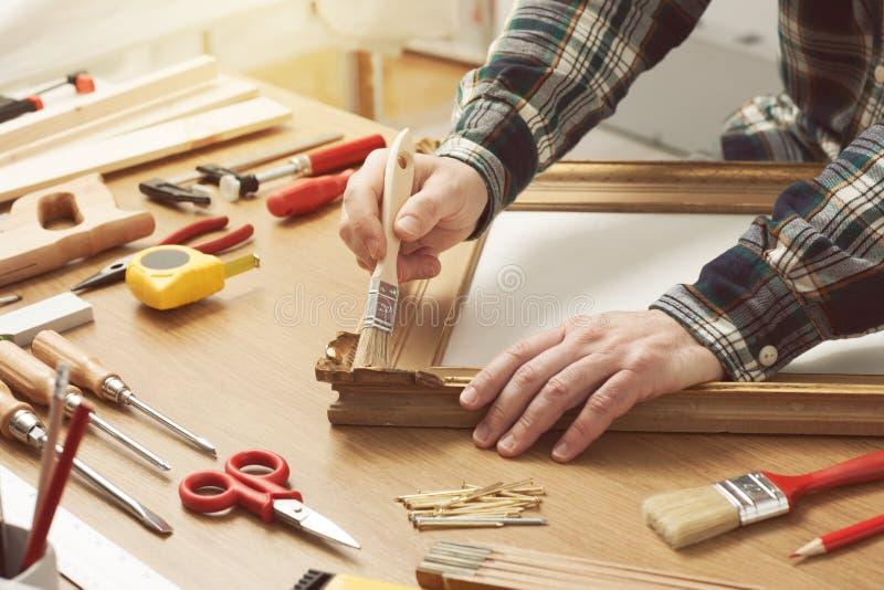 Человек лакируя деревянную рамку дома стоковое изображение