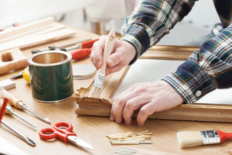 Человек лакируя деревянную рамку дома стоковые изображения