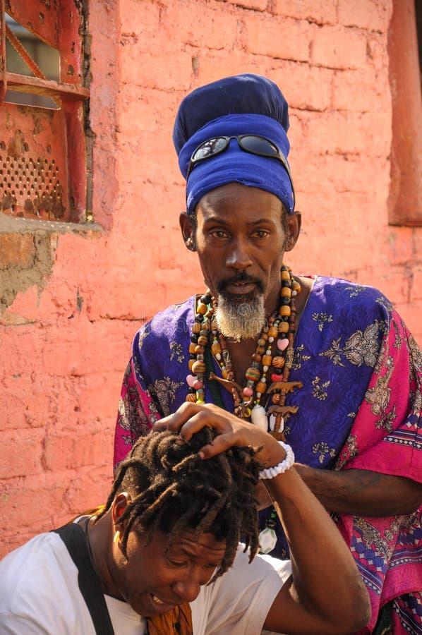 Человек Афро-кубинца ГАВАНЫ, КУБЫ - 20-ое января 2013 делая dreadlock h стоковые фото