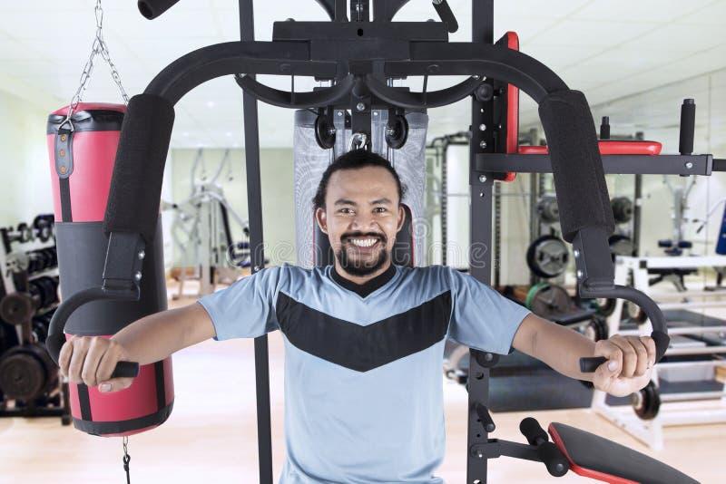 Человек Афро с машиной веса в спортзале стоковые фото