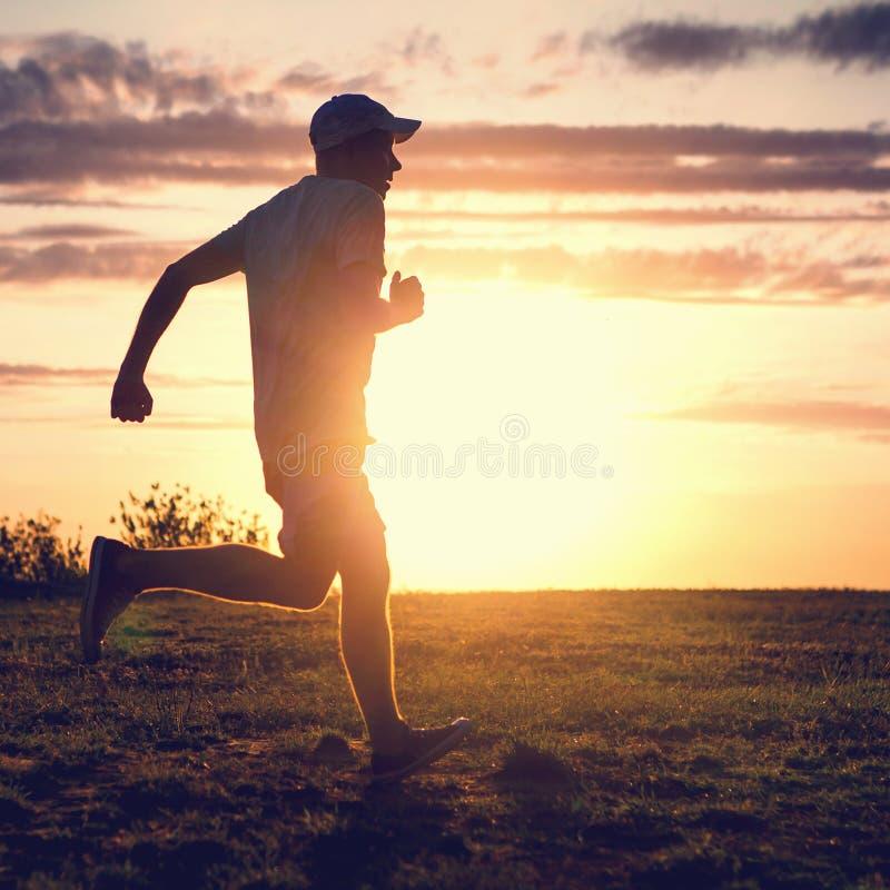 Человек бежать на заходе солнца стоковые фотографии rf