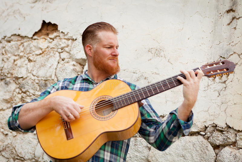 Человек битника при красная борода играя гитару стоковая фотография rf