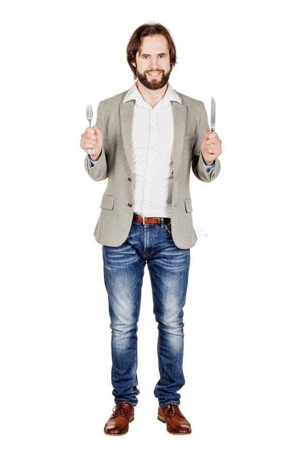Человек бороды держа вилку и нож столового прибора в наличии диета, еда, он стоковые изображения