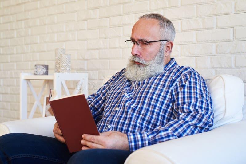 Человек бороды отражательно читая книгу стоковые изображения rf