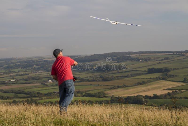 Человек бросая с модельного sailplane над сельской местностью стоковая фотография rf