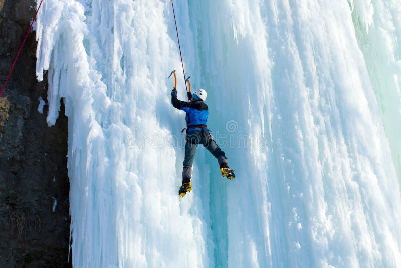 Человек взбираясь, который замерли водопад стоковое изображение rf