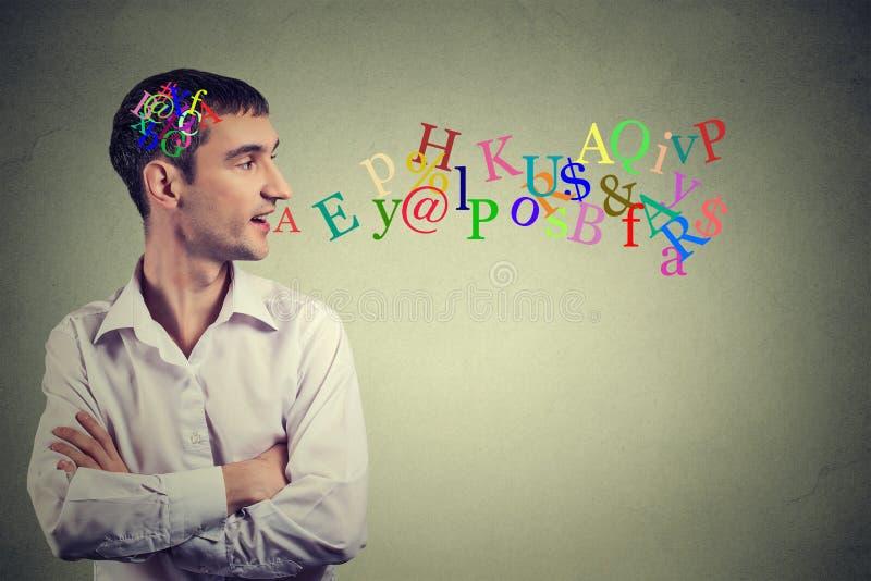 Человек взгляда со стороны разговаривая с письмами алфавита в его голове приходя из открытого рта стоковые изображения rf