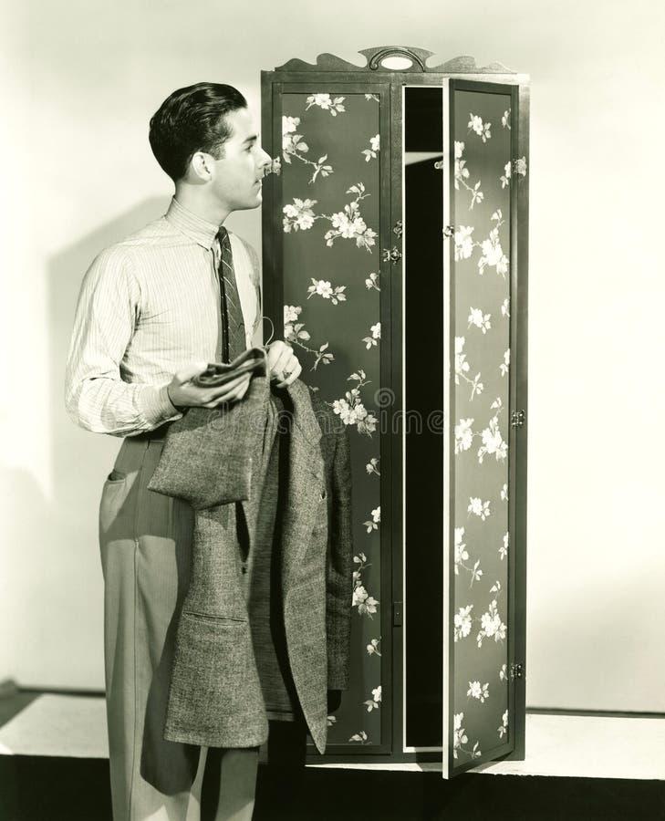 Человек вися вверх блейзер в armoire стоковые изображения