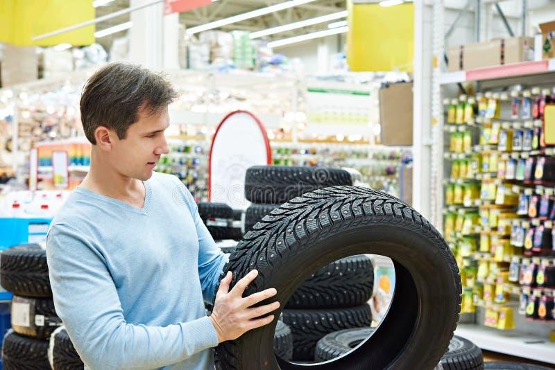 Человек выбирает автошины обитые зимой для автомобиля в супермаркете стоковые фотографии rf
