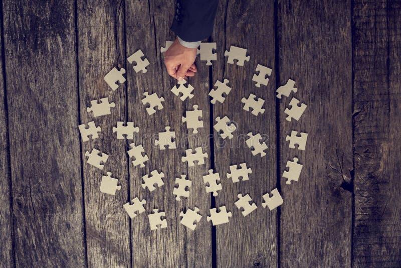 Человек выбирая часть головоломки стоковая фотография rf