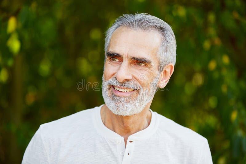 Человек выбытый старшием усмехаясь с утехой стоковые фото