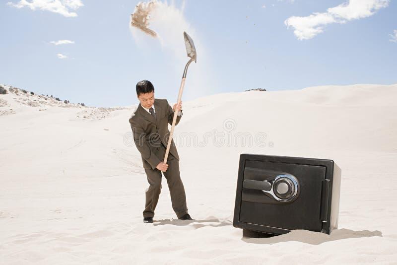 Человек выкапывая сейфом в пустыне стоковое фото rf