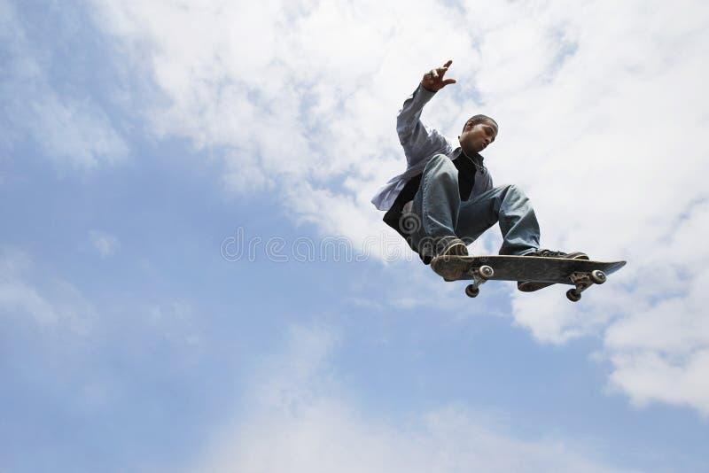 Человек выполняя фокус на скейтборде стоковое изображение