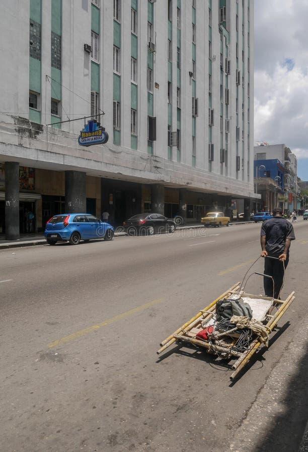 Человек вытягивает деревянную конструкцию в Гаване Кубе стоковое фото