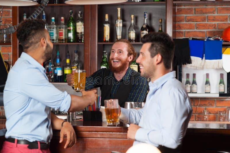 2 человек в баре на счетчике, бармен давая стекло пива, друзей встречая усмехаться парней жизнерадостный стоковое изображение rf