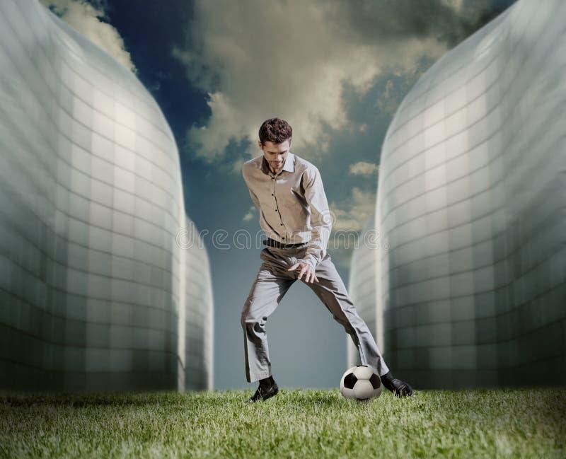 Человек в вскользь костюме играя в футболе около современного здания стоковое фото rf