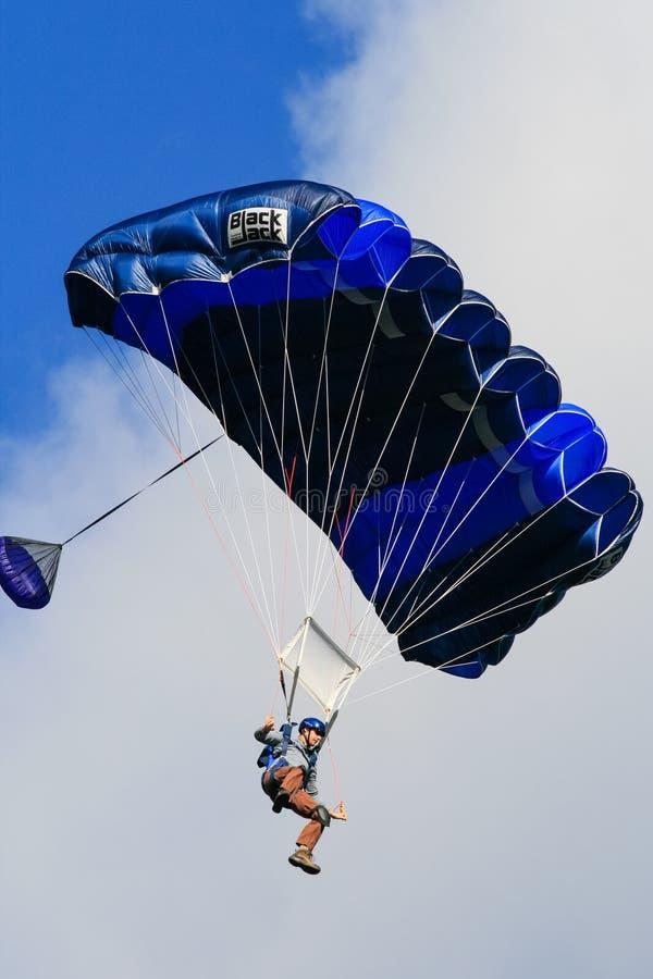 Человек в голубом летании парашюта стоковые изображения rf