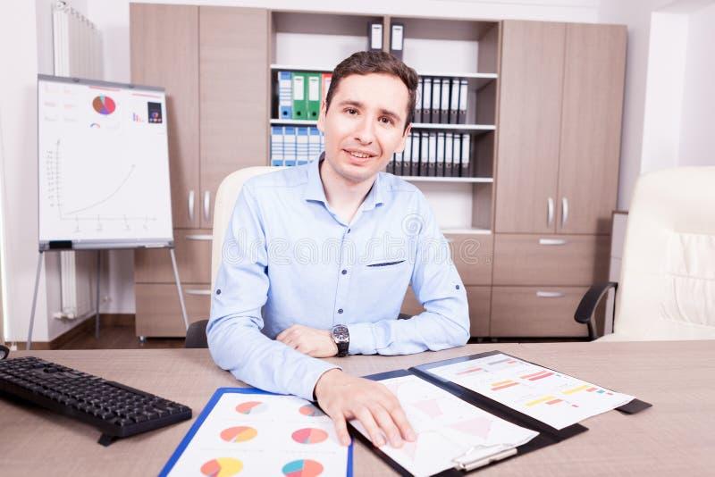 Человек в его offce с папками диаграмм на таблице стоковое фото