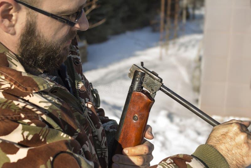 Человек в лесе зимы перезаряжает пневматические оружия Охотник одел в камуфлировании с пневматическим оружием, винтовкой стоковые фото