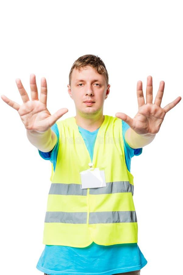 Человек в жилете показывает руки с жестом СТОПА на белизне стоковое фото