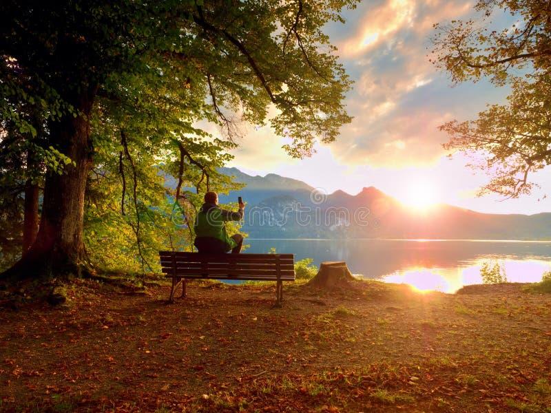 Человек в зеленой внешней куртке принимает фото, сидит на деревянной скамье на озере стоковое изображение rf
