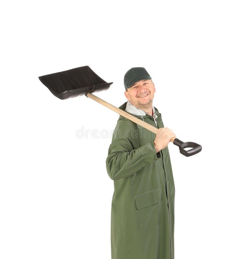 Человек в зеленом пальто с лопаткоулавливателем снега стоковая фотография rf