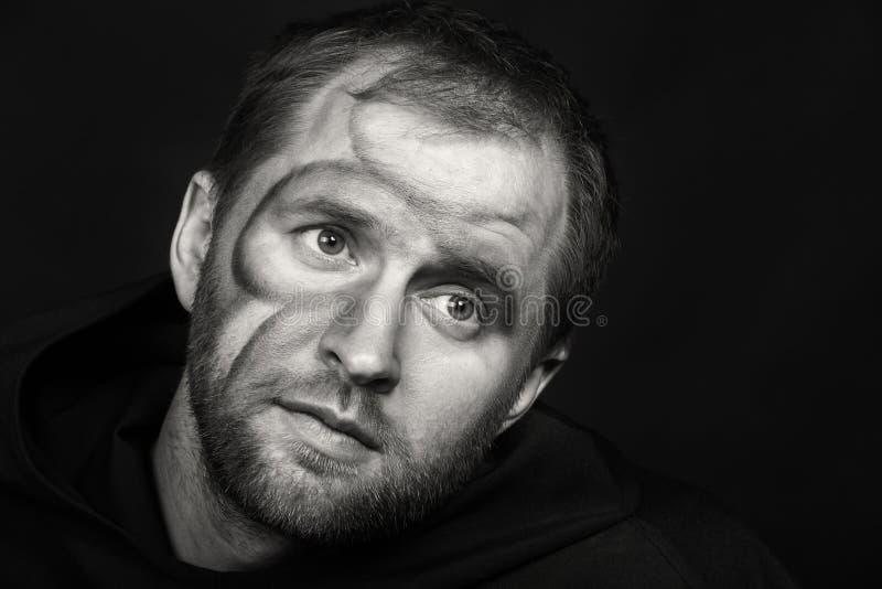 Человек в изображении монаха на темной предпосылке стоковые изображения