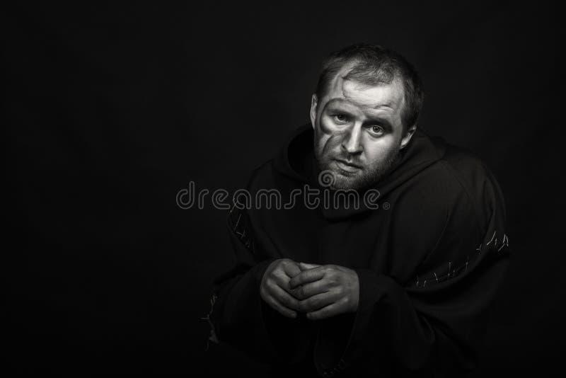 Человек в изображении монаха на темной предпосылке стоковое фото rf