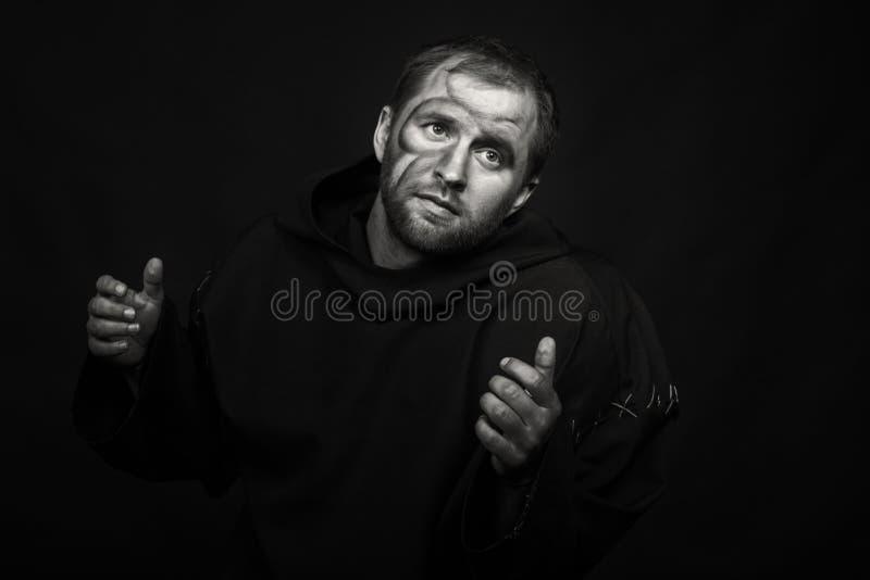 Человек в изображении монаха на темной предпосылке стоковые фотографии rf