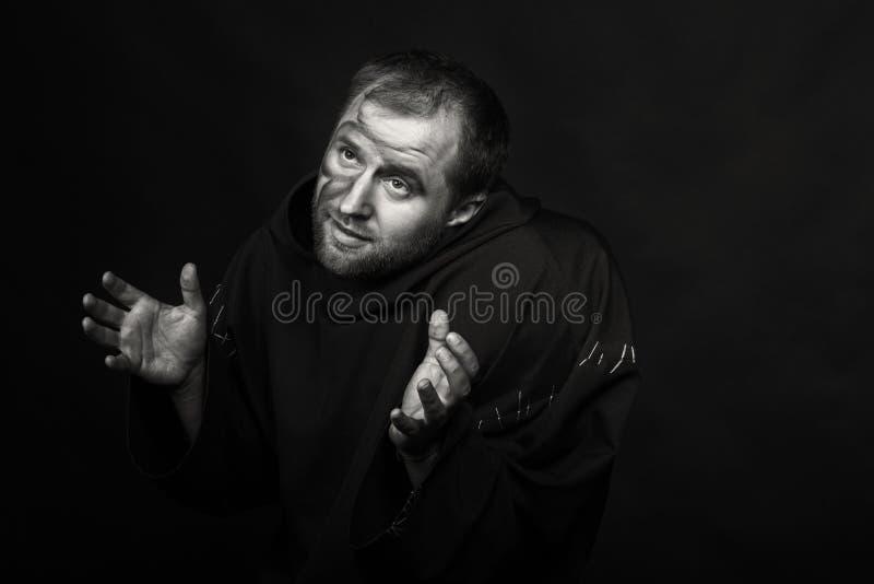 Человек в изображении монаха на темной предпосылке стоковое фото