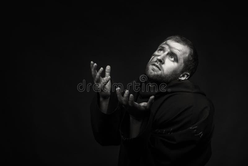 Человек в изображении монаха на темной предпосылке стоковые изображения rf