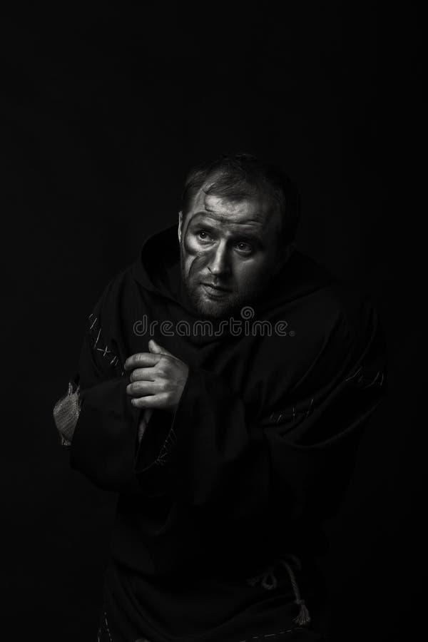Человек в изображении монаха на темной предпосылке стоковые фото