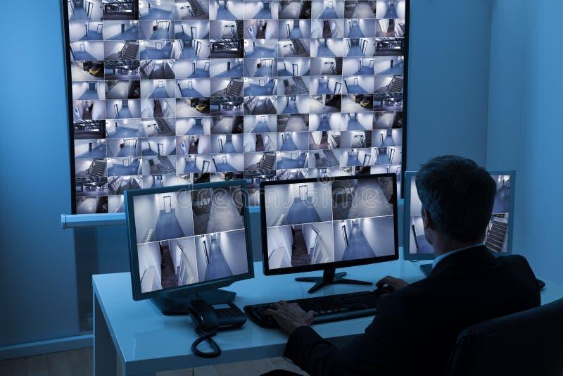 Человек в диспетчерском пункте контролируя отснятый видеоматериал cctv стоковое изображение rf