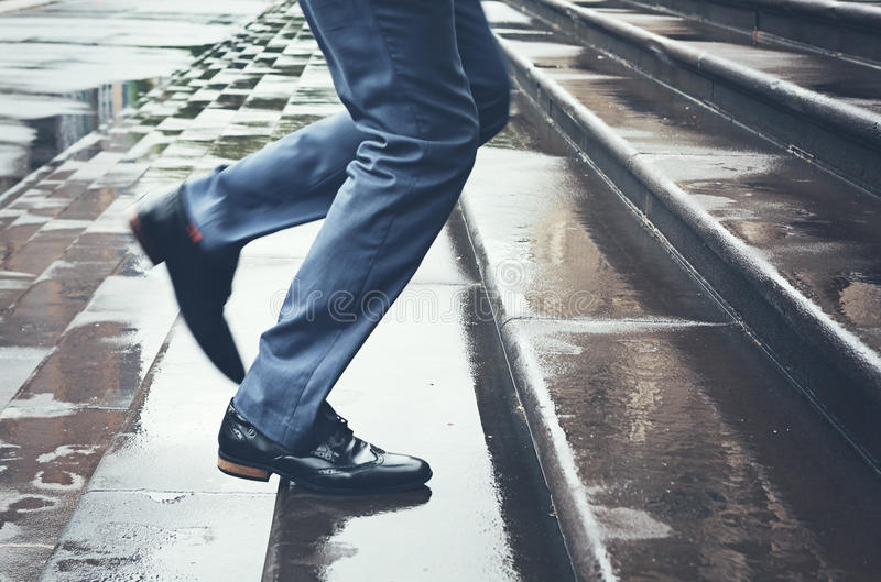 Человек в костюме бежать поздно вверх по шагам в дождь стоковые изображения rf