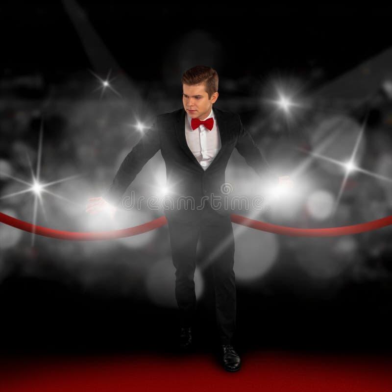 Человек в костюме на красном ковре и прятать от папарацци стоковые изображения
