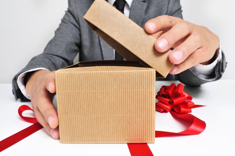 Человек в костюме раскрывая подарок стоковая фотография rf