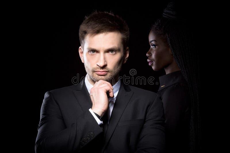 Человек в костюме стоя при рука касаясь его подбородку с темнотой снял кожу с женщины позади стоковая фотография rf