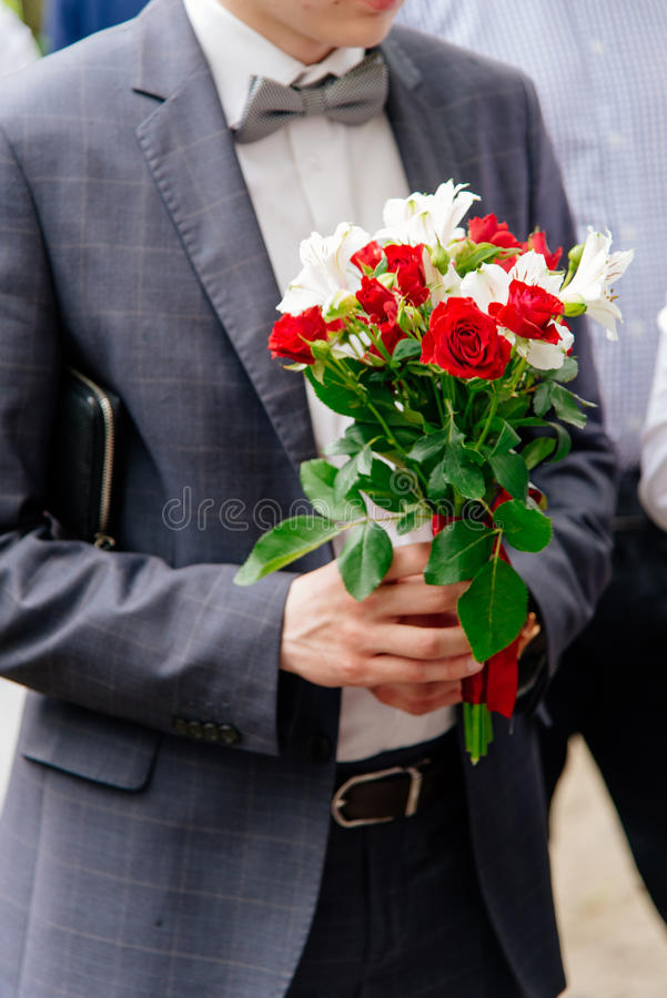 Человек в костюме с цветками в его руках Фокус на bouq цветков стоковые изображения